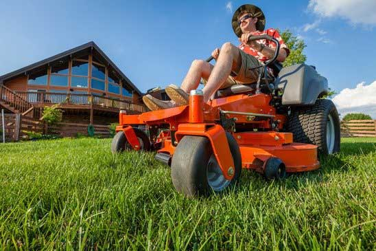 A man is mowing backyard on a riding zero turn lawnmower